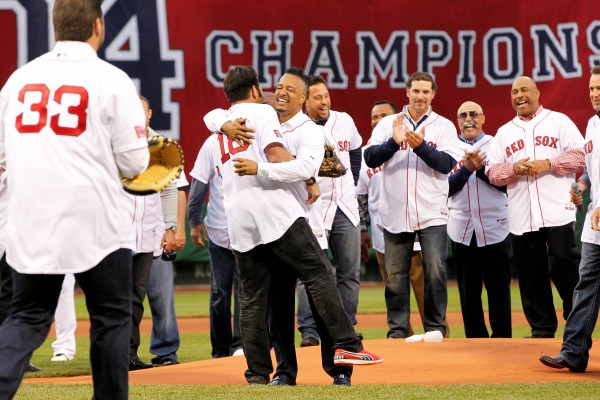 Former Boston Red Sox player Manny Ramirez (right center) embraces former teammate Johnny Damon (left center) after throwing out the first pitch before the game against the Atlanta Braves at Fenway Park in Boston Wednesday night.