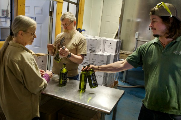 Toni (from left) and Dan Piotti label and pack bottles of Cold River Gin in Freeport recently with Ian MacLeod.