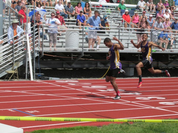 Isaac Yeboah of Cheverus High School lunges across the finish line ahead of his twin brother Elijah to win the 300-meter hurdles at Saturday's Class A track and field championships. The seniors sparked the Stags to the boys team title.