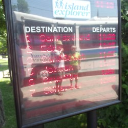Passengers waiting for the Island Explorer bus service are reflected in a digital sign at the village green in Bar Harbor.