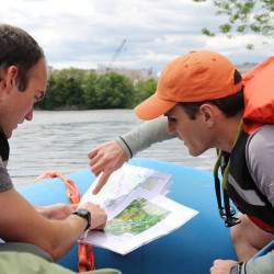 Sam Roy (left) and Brett Gerard, both Ph.D. students at UMaine's School of Earth and Climate Sciences, discuss USGS maps of the Lower Penobscot River on Friday during a research rafting trip down the river to map the bottom composition with sonar.