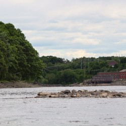 A group of geologists and biologists from the University of Maine, both professors and students, float down by the old Veazie Dam site on the Penobscot River during a Friday research trip to map the substrates on the river's bottom and search for various fish.