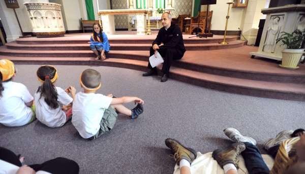 Rev. Seamus Greisbach (center) talks to Vacation Bible School participants at the St. Mary's Church in Augusta.