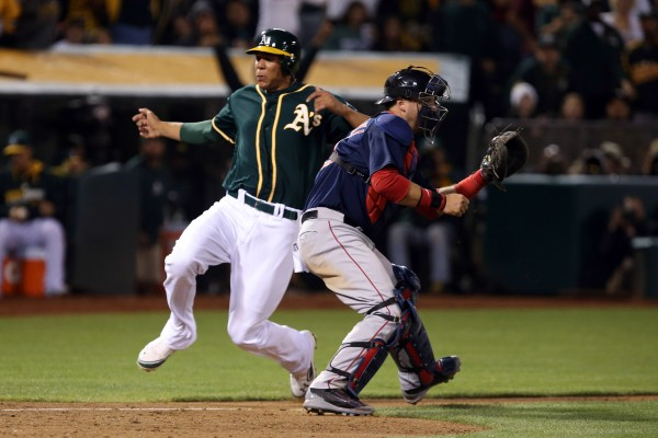 Oakland Athletics first baseman Kyle Blanks (88) slides safely home behind Boston Red Sox catcher A.J. Pierzynski (40) for a run during the eighth inning at O.co Coliseum in Oakland Friday night.