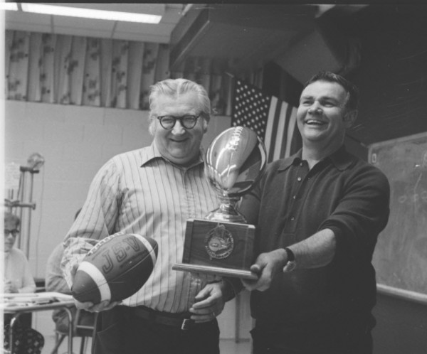 Bangor coach Gerry Hodge (right) receives a trophy from Bangor High School Football Boosters President Mel Maidlow on Nov. 17, 1975.