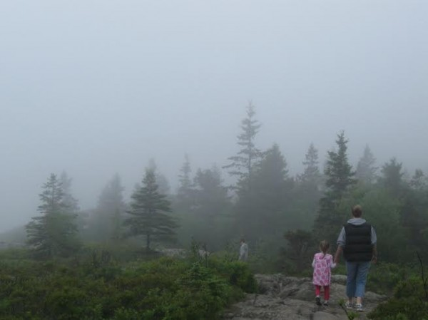 Ann Hartman and her daughter, Emma, cross Great Head in Acadia National Park in the fog.