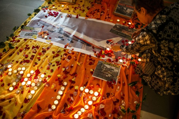 A woman lights candles at a memorial for victims of the downed Malaysia Airlines Flight MH17 in Kuala Lumpur July 18, 2014.