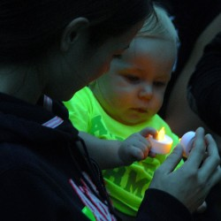 Katrina Hutchinson, 22, of Newport, holds 9-month-old Eli Richcreek during a vigil in honor of Danielle Bertolini at Cascade Park in Bangor on Saturday, July 19, 2014.