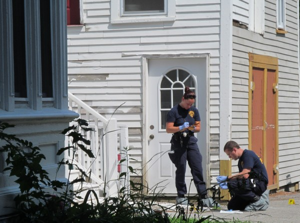 Two Maine State Police crime scene analysts work outside the 19 Western Ave. home in Biddeford on Monday where two men were shot Sunday night.