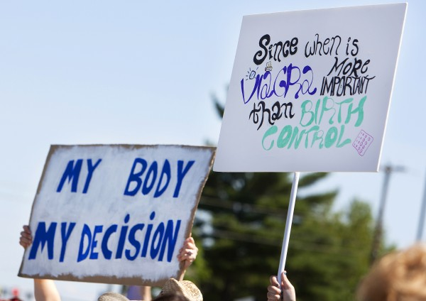 Protestors hold up signs during a protest against the recent Supreme Court decision about birth control and Hobby Lobby on Saturday outside the Bangor Hobby Lobby.