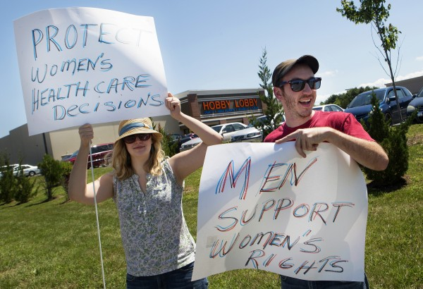 Sydney Bence (left) and Adam Swenson show their support for women's rights during a protest against the recent Supreme Court decision about birth control and Hobby Lobby on Saturday outside the Bangor Hobby Lobby.