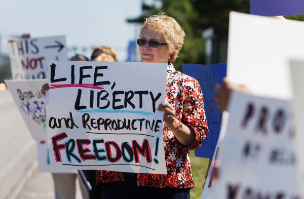 Laurie Fogelman holds up a sign during a protest against the recent Supreme Court decision about birth control and Hobby Lobby on Saturday outside the Bangor Hobby Lobby.