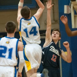 Washburn's Mitchell Worcester (center) drives to the hoop against Bangor Christian's Seth Pearson (right) at the Bangor Auditorium in 2013.