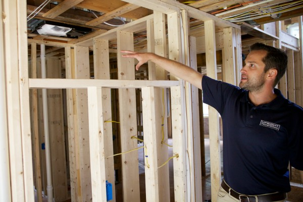 On Tuesday, Josh Wojcik of Upright Properties points to where one of a pair of heat pumps will be installed in a house in Yarmouth his company is renovating.