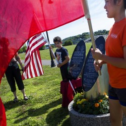 Ethan Schrader (left), 12, and Melissa Tian, 12, hold American and Chinese flags next to the granite sister city monument at Bangor Waterfront Friday. Students from around the area will travel to China for three weeks as part of an immersion program. The group will present an exact replica of the monument to their Chinese host officials, along with a key to the city of Bangor.