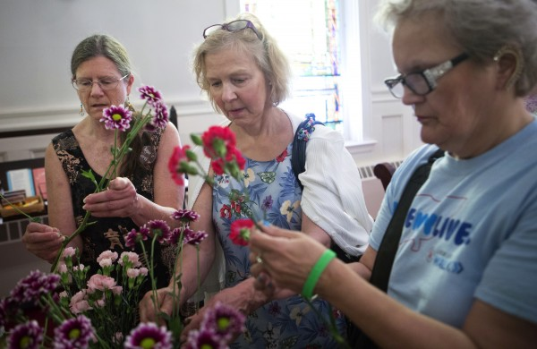 Laurie Cartier (left), Anne Perkins (center) and Beverly Reeves select flowers to be dropped into the Kenduskeag Stream after a church service on Sunday at the Unitarian Universalist Society in Bangor to remember the 30th anniversary of the death of Charlie Howard.
