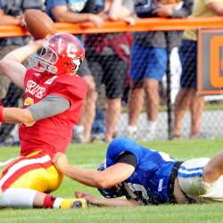 Benjamin Lucas from Cony High School tries to get rid of the ball as Cody Gibbons from Lake Region High School takes him down in the first half of the 2014 Lobster Bowl Saturday in Biddeford. Lucas was ruled down on the field and Gibbons was credited with a quarterback sack.