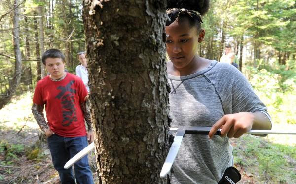 Jaiden Veal of Pleasant Point measures the diameter of a spruce tree during the Wabanaki Youth Science Program in Winter Harbor. The week-long program teaches native high school students about the scientific study of natural resources and combines them with traditional Native American culture.