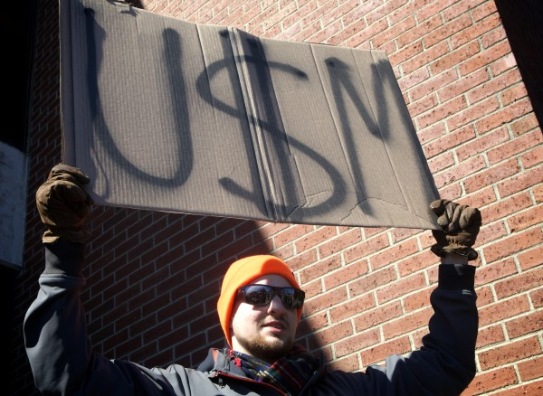 Dan Keller, a business and economics major at the University of Southern Maine, joins a protest in Portland opposing deep cuts proposed by President Theo Kalikow in this March 2014 file photo.