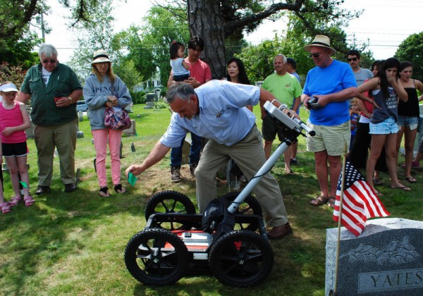 Descendants of Col. Ezekiel Cushing, including Anil Melwani (center), with his daughter Clara, his wife, Gloria Kui Melwani, and his mother, Jackie Cushing Gulhaugen (left), watch Glen Vaillancourt as he scans Cushing's unmarked grave Saturday at the Mount Pleasant Cemetery on Cottage Road in South Portland.