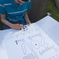 An Orono High School student works on a poster at a Wednesday protest in support of music teacher and orchestra director Waldo Caballero, who is also the boys soccer coach. Caballero may lose his job because he failed to pass a state-required teacher certification test by two points.