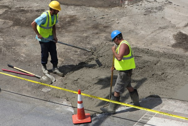 A construction crew works to lay concrete Tuesday near the intersection of Main Street and  Lincoln Street in Bangor.