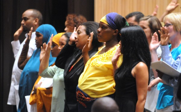People take the Oath of Allegiance during a naturalization ceremony at the Gracie Theater at Husson University on Thursday.