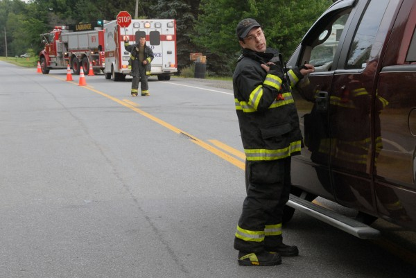 LaGrange Assistant Fire Chief Mike Bacon stops a vehicle near 5572 Bennoch Road in LaGrange on Sunday. It was one of two places where firefighters or police had traffic stopped on in response to a police standoff with Lewis Conlogue of LaGrange.