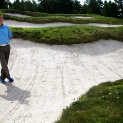 "Doug Van Wickler stands in one of the four bunkers that stand between the tee and the green on hole number four at The Woodlands Club in Falmouth. The sand traps are known locally as the ""coffins."""
