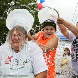Jessie Savage (right) dumps ice water on Hunter Klenowski (center), 12, who dumps water on Heidi Klenowski as part of the ASL Ice Bucket Challenge on Friday at Carrier's restaurant in Bucksport.