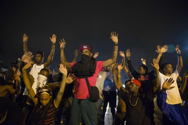 Demonstrators confront police with their arms raised early Saturday during ongoing demonstrations to protest against the shooting of Michael Brown in Ferguson, Missouri.