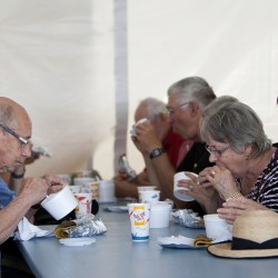 People enjoy chicken stew and ployes Friday during the 2014 Acadian World Congress in Edmundston. Chicken stew and ployes are traditional Acadian dishs.