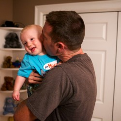 Chad Bilodeau kisses his son Carter, 11 months, before nap time on Friday in Gray. Carter's room has blackout curtains and a white noise machine to help him sleep.