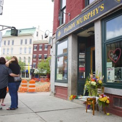 People mourn the deaths of Phill Carter and Roxanne Papken Wednesday afternoon at Paddy Murphy's in downtown Bangor. Several businesses closed for the day in Bangor after the deaths of the two Paddy Murphy's employees. Carter and Papken were killed in a crash on Route 1A in Dedham on Tuesday evening.