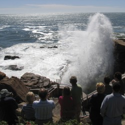 Tourists admire spray from waves crashing into Thunder Hole in Acadia National Park  after Hurricane Irene in this 2011 photo.