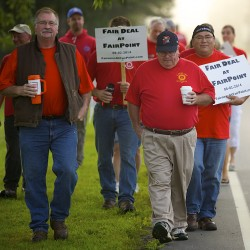 """FairPoint technician and union mobilizer Jim Feeney (left) marches alongside Bob Toole on Aug. 12 during an informational picket in front of FairPoint Communications in Bangor. Feeney said Friday that FairPoint workers in Bangor were on ""heightened alert"" in case a strike is called after the company stepped away from bargaining early Thursday morning."