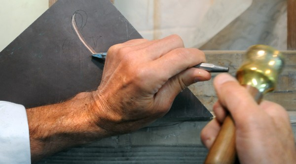 Doug Coffin demonstrates cutting a letter into stone at his shop in Belfast.