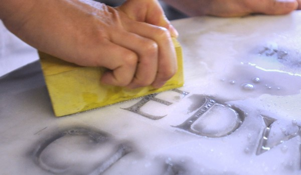 Sigrid Coffin demonstrates how the excess coloring is sanded from marble to give the letters a 3-D look.
