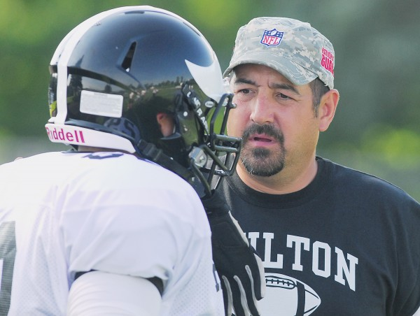 Houlton High School Football coach Brian Reynolds talks with a player before the start of a scrimmage against Bucksport High School Monday at Carmichael Field in Bucksport.
