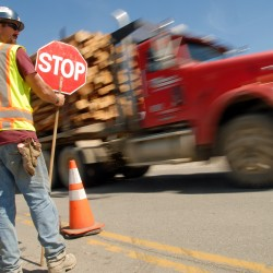 Mike Mulcahy directs traffic on West Broadway in Lincoln past a natural gas pipeline installation point Wednesday, Aug. 20, 2014.