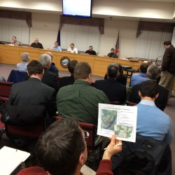 An Orono resident looks at a map of the proposed site for a 270-unit student housing development at a public hearing in March.