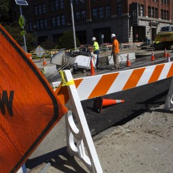 Construction crews work to cut up the road near the intersection of State and Exchange streets in Bangor on Tuesday.