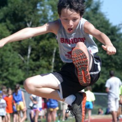 Bangor Track Club's Joshua Bohm stretches out in the boys ages 9-10 long jump during the U.S. Track and Field's state championships Saturday at Windham High School.