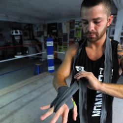 Boxer Brandon Berry of West Forks puts on his hand wrap before a workout in July at Wyman's Boxing Club in Stockton Springs.
