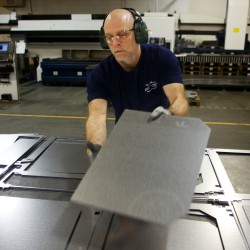 Mike Mattison separates sheet metal parts at Jotul North America's wood and gas stove manufacturing facility in Gorham on Feb. 21, 2014.