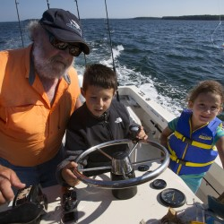 Will Caron (center), 9, gets some help from Capt. Pete Douvarjo (left) while driving his boat as sister Paige Caron (right), 6, watches during a fishing trip Aug. 26.