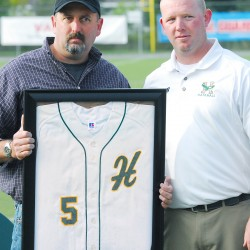 David Winkin (left), holding a plaque containing his father's jersey, and Jason Harvey attend a Husson University ceremony for the legendary baseball coach John Winkin on Saturday in Bangor.