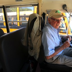 "Gerald ""Red"" Briggs sits in a school bus before leaving the parking lot to pick up students in Hampden."