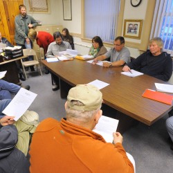 People listen to the meeting of the East Millinocket Board of Selectmen (sitting around table) Jan. 27 at the town office.