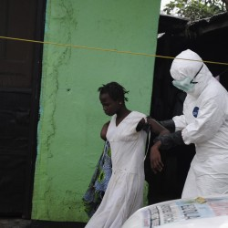 A health worker brings a woman suspected of having contracted the Ebola virus to an ambulance in Monrovia, Liberia, September 15, 2014. Airlines have halted many flights into and around West Africa, where governments have closed some borders and imposed travel restrictions in a bid to fight an Ebola outbreak that has killed over 2,400 people.